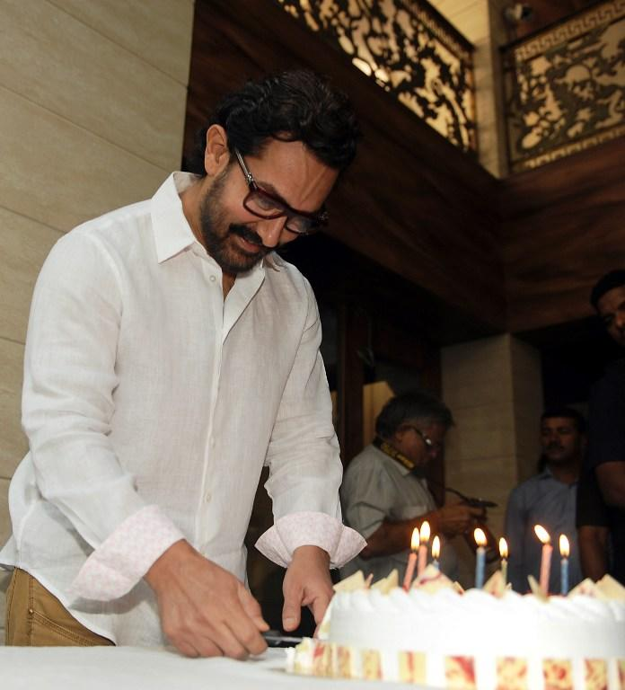 <p>Indian Bollywood actor and producer Aamir Khan poses for the media during the cake cutting on his 52nd birthday, at his residence in Mumbai on March 14, 2017. / AFP PHOTO / STR </p>