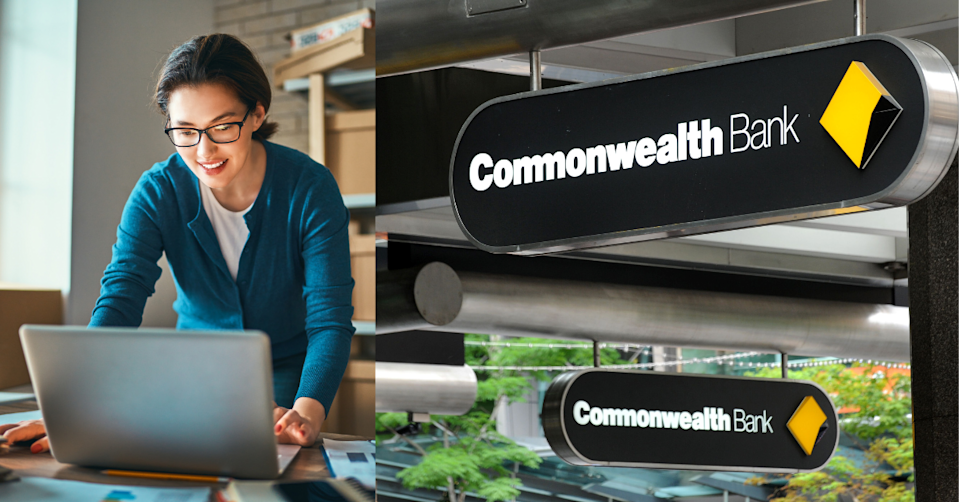 A woman works on her laptop in front of boxes to the left and the Commonwealth Bank sign to the right.