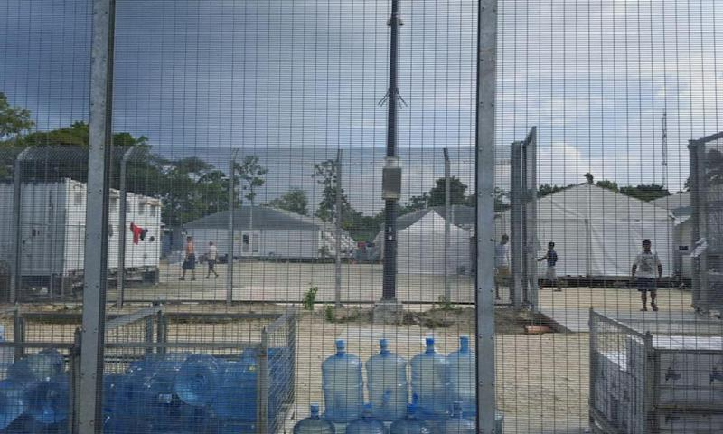 Detainees walk around the compound among water bottles inside the Manus Island detention centre in Papua New Guinea,