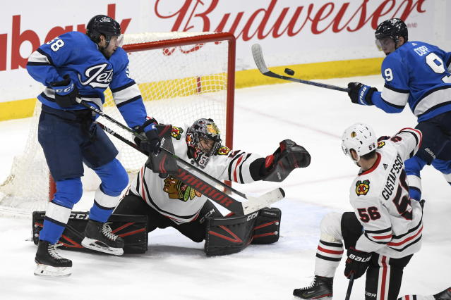 Winnipeg Jets' Andrew Copp (9) and Jansen Harkins (58) looks for rebound in front of Chicago Blackhawks' goaltender Corey Crawford (50) during third period NHL hockey action in Winnipeg, Manitoba on Sunday, Feb. 9, 2020. (Fred Greenslade/The Canadian Press via AP)