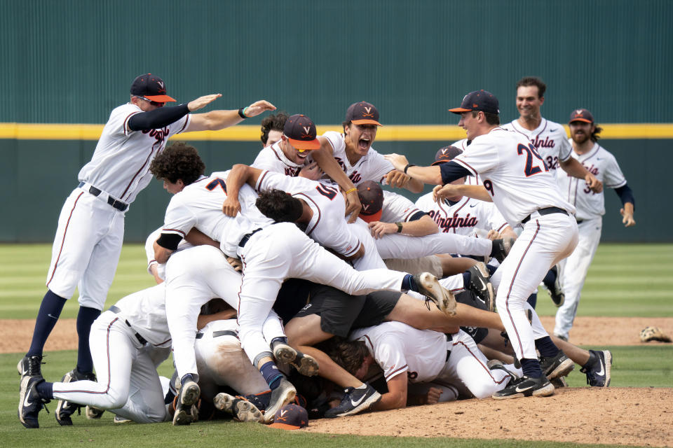 Virginia players celebrate after an NCAA college baseball tournament super regional game against Dallas Baptist, Monday, June 14, 2021, in Columbia, S.C. (AP Photo/Sean Rayford)