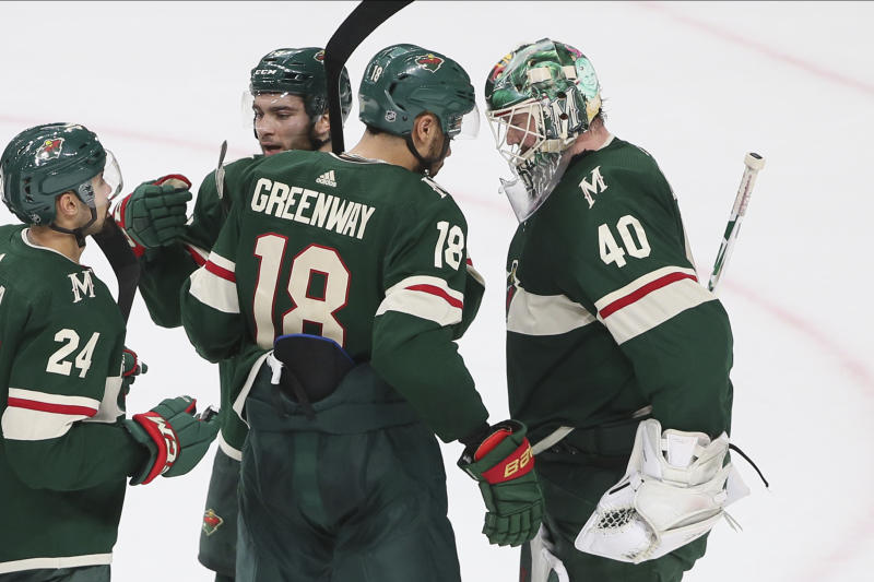 Minnesota Wild's Devan Dubnyk, right, is congratulated by Jordan Greenway and others after the Wild defeated the Detroit Red Wings 4-2 in an NHL hockey game Wednesday, Jan. 22, 2020, in St. Paul, Minn. Greenway scored a goal in the first period. (AP Photo/Jim Mone)