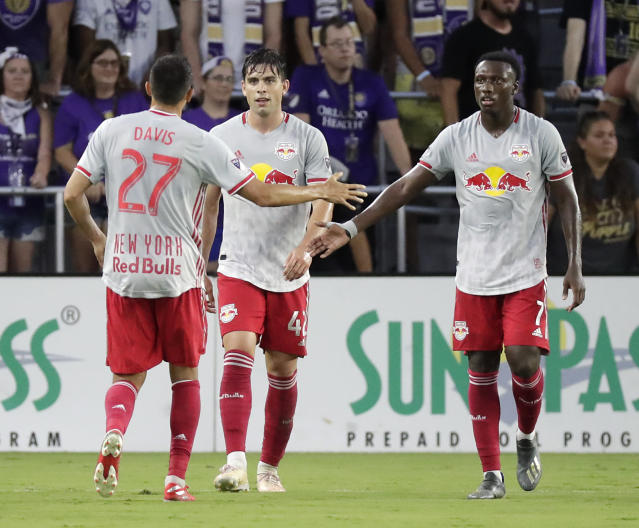 New York Red Bulls' Brian White, center, celebrates his goal against Orlando City with teammates Sean Davis (27) and Derrick Etienne Jr. (7) during the first half of an MLS soccer match, Sunday, July 21, 2019, in Orlando, Fla. (AP Photo/John Raoux)