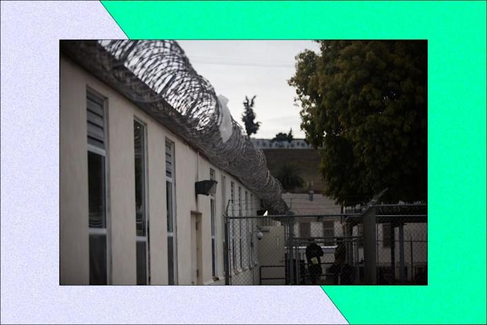 Exterior of a prison with barbed wire lining the top of the wall