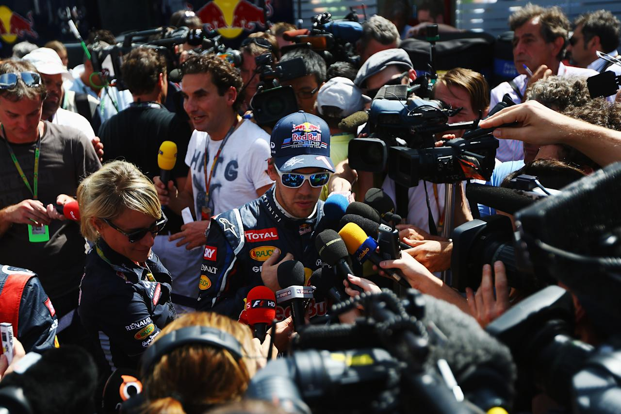 SAO PAULO, BRAZIL - NOVEMBER 23:  Sebastian Vettel of Germany and Red Bull Racing is interviewed by the media during practice for the Brazilian Formula One Grand Prix at the Autodromo Jose Carlos Pace on November 23, 2012 in Sao Paulo, Brazil.  (Photo by Paul Gilham/Getty Images)