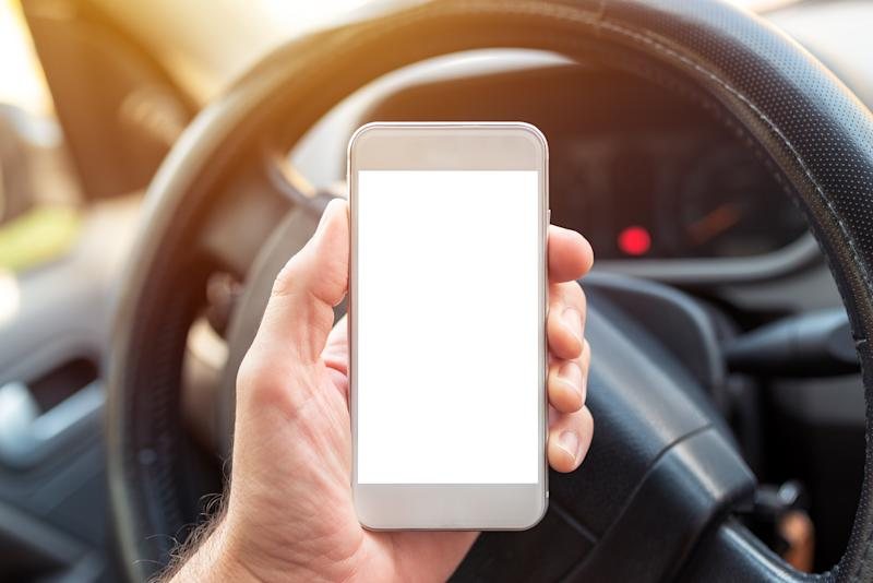 Using smartphone in car, mock up blank screen of mobile phone device in hand of adult caucasian male