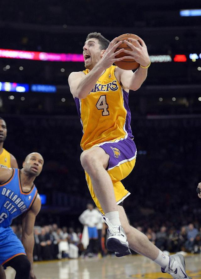 Los Angeles Lakers forward Ryan Kelly, right, goes up for a shot as Oklahoma City Thunder point guard Derek Fisher stands near during the first half of an NBA basketball game Thursday, Feb. 13, 2014, in Los Angeles. (AP Photo/Mark J. Terrill)