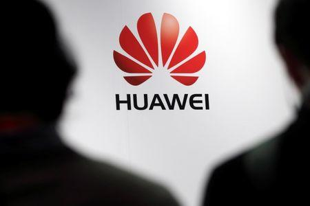 Journalists attend the presentation of the Huawei's new smartphone in Paris