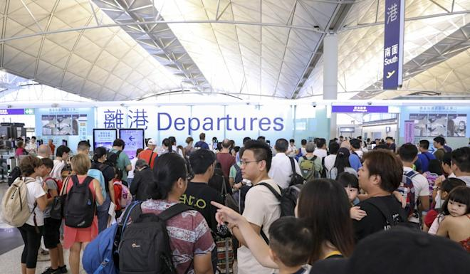 Travellers try to get on their flights as major disruption mires the airport for the third day in a row. Photo: K.Y. Cheng