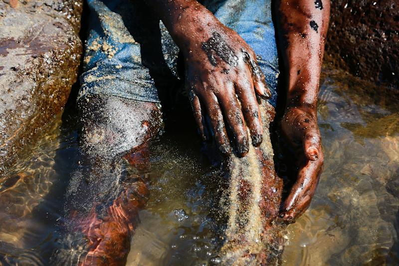 A boy cleans his legs after removing oil spilled on Itapuama beach located in the city of Cabo de Santo Agostinho, Pernambuco state, Brazil, on October 21, 2019. - Large blobs of oil staining more than 130 beaches in northeastern Brazil began appearing in early September and have now turned up along a 2,000km stretch of the Atlantic coastline. The source of the patches remain a mystery despite President Jair Bolsonaro's assertions they came from outside the country and were possibly the work of criminals. (Photo by LEO MALAFAIA / AFP) (Photo by LEO MALAFAIA/AFP via Getty Images)