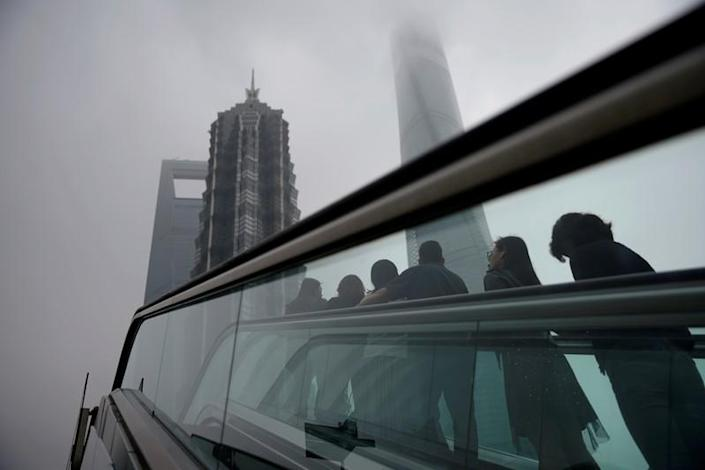 FILE PHOTO: People ride an escalator near skyscrapers at Lujiazui financial district in Shanghai