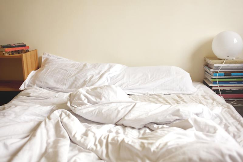 Unmade bed in the morning showing clean white bedding and pillows.