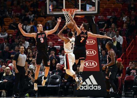Dec 13, 2017; Miami, FL, USA; Portland Trail Blazers guard CJ McCollum (3) shoots the ball as Miami Heat center Kelly Olynyk (9) and guard Goran Dragic (7) defend during the first half at American Airlines Arena. Steve Mitchell-USA TODAY Sports
