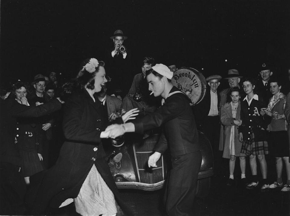 <p>A sailor dances with a laughing women in Times Square as a brass band strikes up a tune on the hood of a car.</p>
