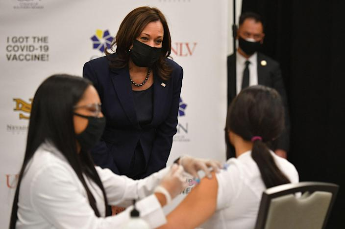 US Vice President Kamala Harris watches a health worker giving a Covid-19 vaccine to a woman at the University of Nevada in Las Vegas on March 15.