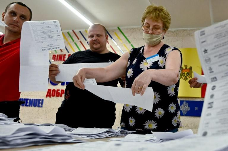Members of a local electoral commission count ballots at a polling station during parliamentary elections in Chisinau
