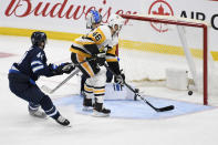 Pittsburgh Penguins' Zach Aston-Reese (46) scores a short-handed goal on Winnipeg Jets goaltender Laurent Brossoit (30) during the third period of an NHL hockey game, Sunday, Oct. 13, 2019, in Winnipeg, Manitoba. (Fred Greenslade/The Canadian Press via AP)