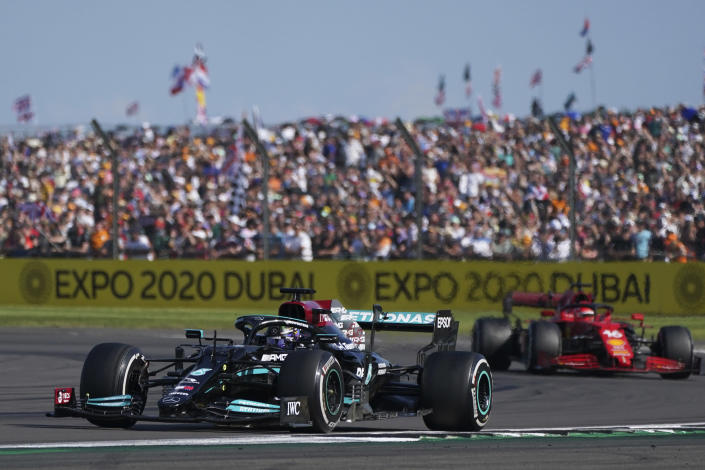 Mercedes driver Lewis Hamilton of Britain steers his car ahead of Ferrari driver Charles Leclerc of Monaco, right, during the British Formula One Grand Prix, at the Silverstone circuit, in Silverstone, England, Sunday, July 18, 2021. (AP Photo/Jon Super)