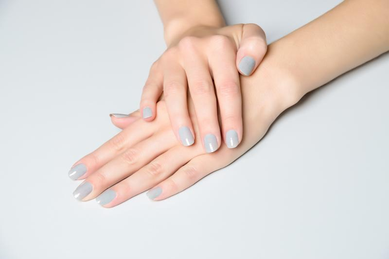 Pair of female manicured hands with short nails on white table