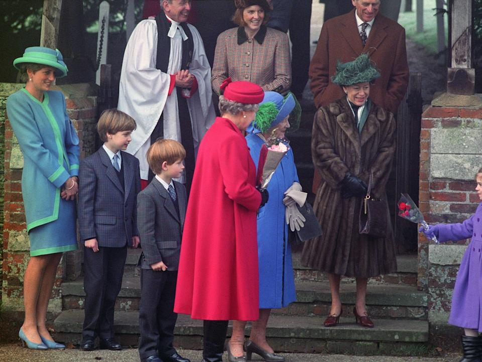 An adorable Prince William and Prince Harry can be seen standing beside their mother, Princess Diana, as a little girl gives flowers to the Queen Mother in 1991. Photo: Getty Images