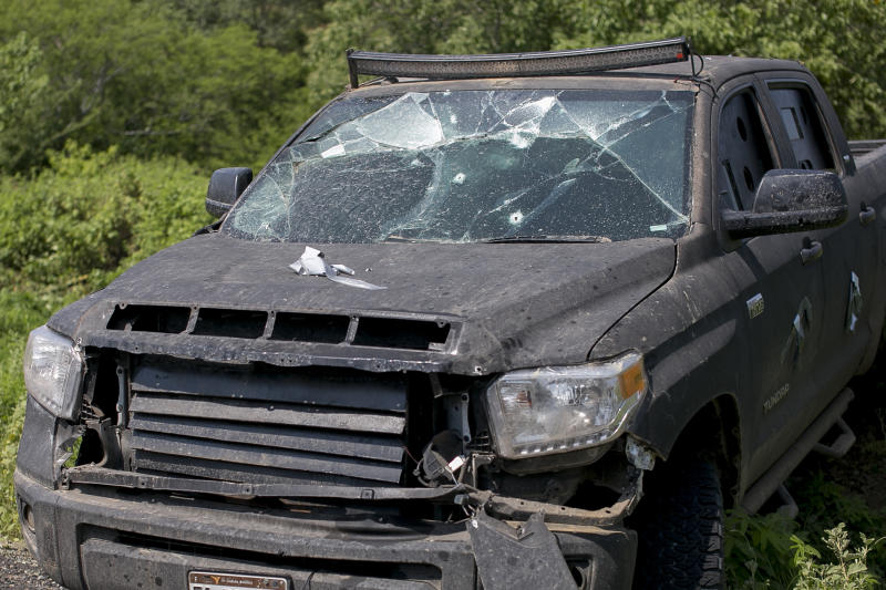 A bullet ridden home-made armored truck lays abandoned on the side of the road, in the outskirts of Tepalcatepec, Michoacan state, Mexico, Saturday, Aug. 31, 2019. Heavily armed bands clashed Friday, for control of Tepalcatepec, leaving at least 9 dead, according the Ministry of Public Security and Citizen Protection. (AP Photo/Armando Solis)