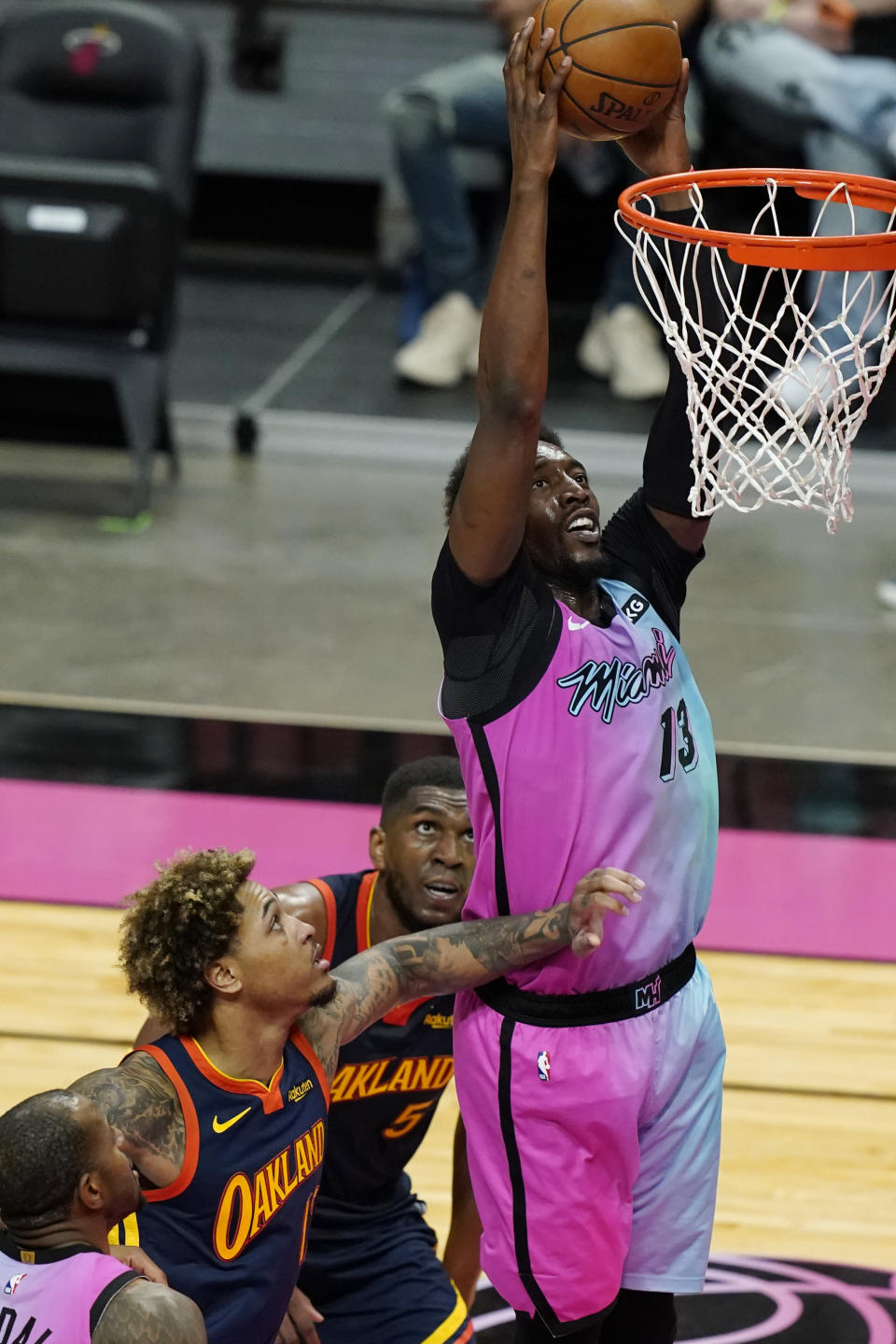 Miami Heat center Bam Adebayo (13) dunks the ball over Golden State Warriors center Kevon Looney (5) and guard Kelly Oubre Jr., during the second half of an NBA basketball game, Thursday, April 1, 2021, in Miami. (AP Photo/Marta Lavandier)
