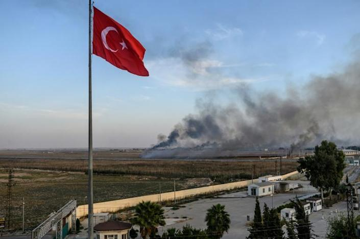 In a picture taken from the Turkish side of the border, smoke rises from the Syrian town of Tal Abyad, one of the main Kurdish-controlled towns in the area coveted by Ankara (AFP Photo/BULENT KILIC)