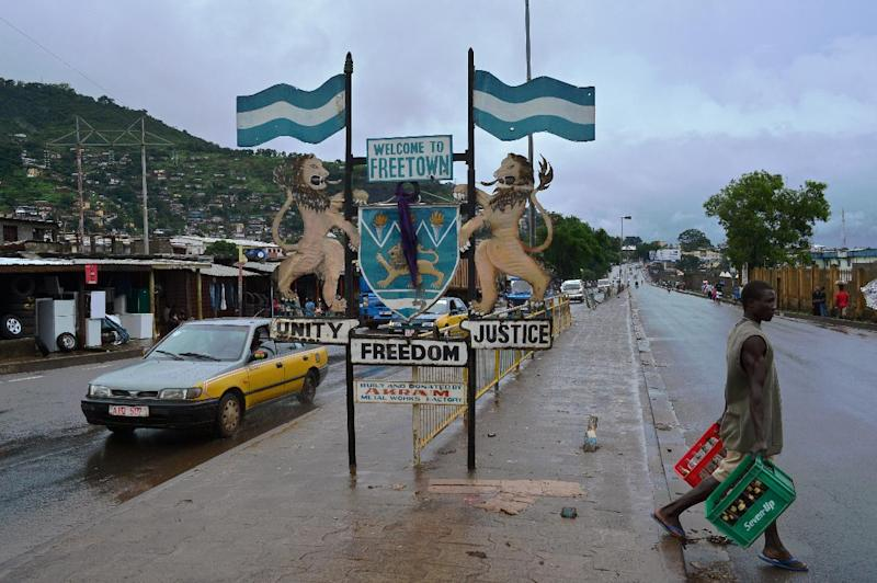 A man walks past a city sign in Freetown on August 13, 2014 (AFP Photo/Carl De Souza)