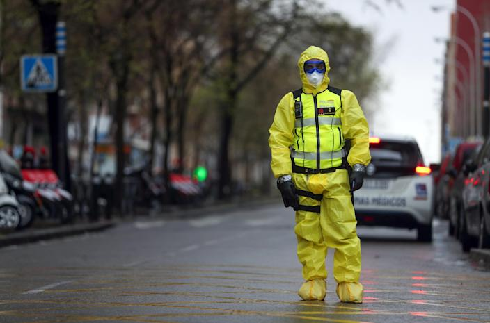 A member of the Emergency Military Unit waits for a bus in which COVID-19 patients were being transferred to another hospital in Madrid on April 1. (Susana Vera/Reuters)