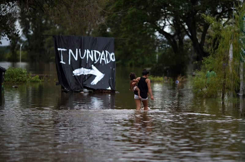 A woman carries her baby through a flooded area of Concordia, Entre Rios province, Argentina on December 29, 2015 (AFP Photo/)