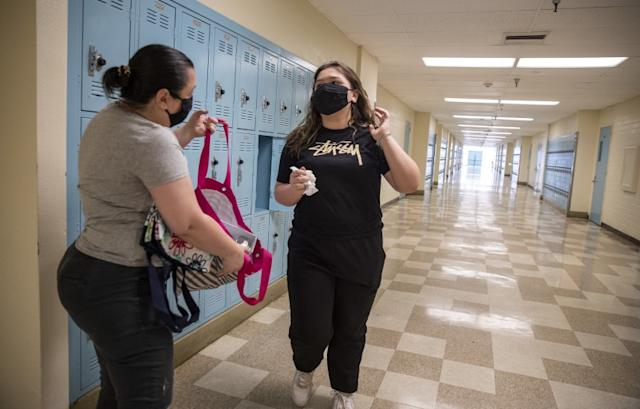 """Jamie Zamudio, left, helps her daughter Isabella, 14, clean out her locker at El Camino Real Charter High School in Woodland Hills on April 30, after the school was closed. <span class=""""copyright"""">(Los Angeles Times)</span>"""