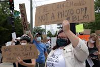 WASHINGTON, DC - JUNE 02: (EDITOR'S NOTE: Image contains profanity.) Demonstrators stage a protest near the Saint John Paul II National Shrine, where President Donald Trump planned a visit, in response to the death of George Floyd while under police custody June 2, 2020 in Washington, DC. President Trump laid a ceremonial wreath and observed a moment of silence to the statue of Saint John Paul II during his visit at the shrine. (Photo by Alex Wong/Getty Images)