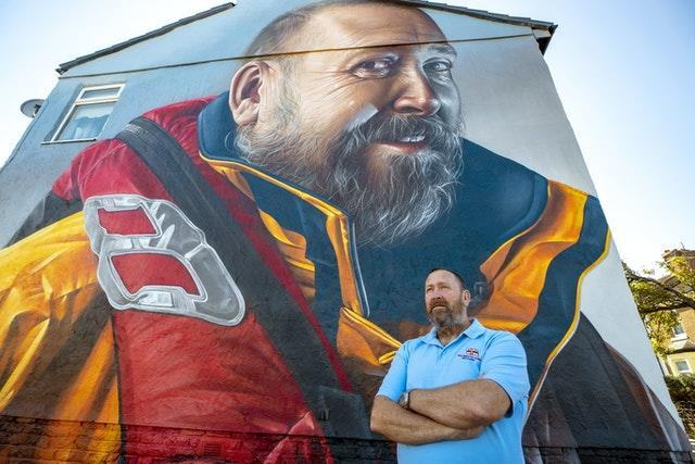 RNLI volunteer Mike Jones in front of a mural of him to honour of his 40 years of service