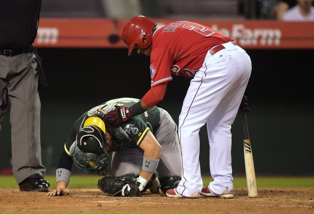 Los Angeles Angels' Erick Aybar, right, checks on Oakland Athletics catcher Derek Norris after Aybar hit him in the head with a bat during a swing in the fourth inning of a baseball game, Tuesday, June 10, 2014, in Anaheim, Calif. (AP Photo/Mark J. Terrill)