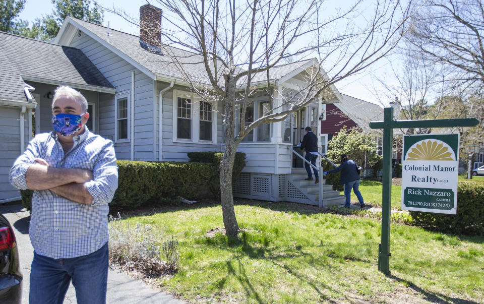 "REVERE, MA - MAY 2: Rick Nazarro of Colonial Manor Realty waits in the driveway as a couple enters a property he is trying to sell during a ""controlled"" open house on May 2, 2020 in Revere, MA. Nazarro says he gets there early to open every door and wipe down all surfaces so interested buyers don't have to touch anything, also he only lets one party in at a time encouraging others to practice social distancing. (Photo by Blake Nissen for The Boston Globe via Getty Images)"