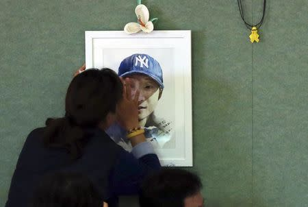 A family member of a missing passenger onboard the sunken ferry Sewol, touches her son's portrait as she cries at a gym in Jindo November 11, 2014. REUTERS/Park Cheol-hong/Yonhap