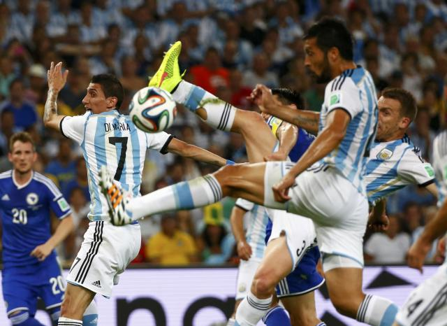 Argentina's Angel Di Maria, Ezequiel Garay and Argentina's Hugo Campagnaro (L-R) lunge for the ball during the 2014 World Cup Group F soccer match against Bosnia and Herzegovina at the Maracana stadium in Rio de Janeiro June 15, 2014. REUTERS/Michael Dalder (BRAZIL - Tags: SOCCER SPORT WORLD CUP)