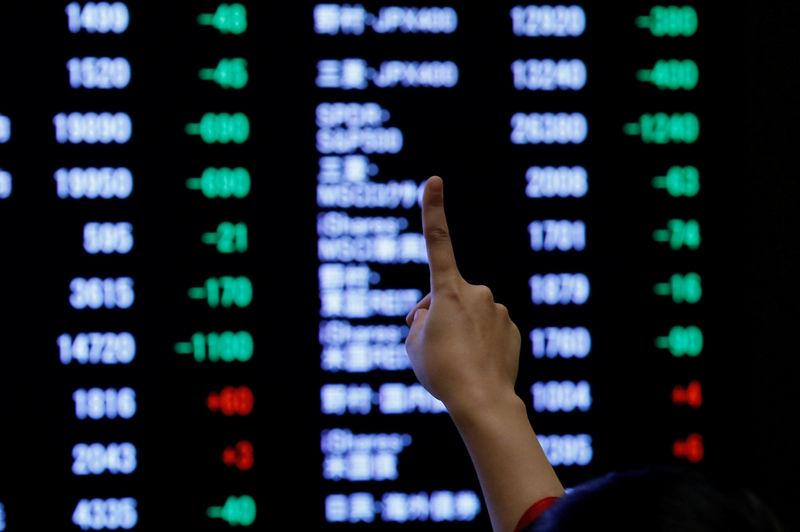 FILE PHOTO: A woman points to an electronic board showing stock prices as she poses in front of the board after the New Year opening ceremony at the Tokyo Stock Exchange (TSE), held to wish for the success of Japan's stock market, in Tokyo