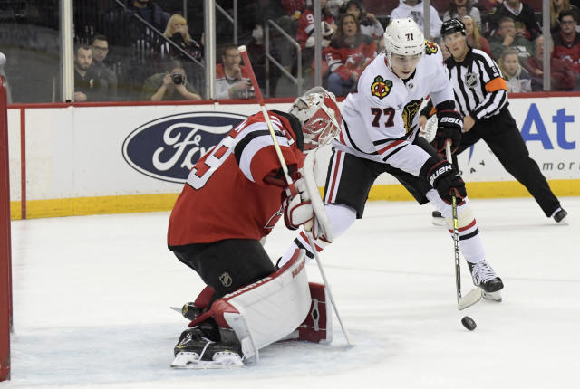 Chicago Blackhawks center Kirby Dach (77) attempts to shoot against New Jersey Devils goaltender Mackenzie Blackwood (29) during the first period of an NHL hockey game Friday, Dec. 6, 2019, in Newark, N.J. (AP Photo/Bill Kostroun)