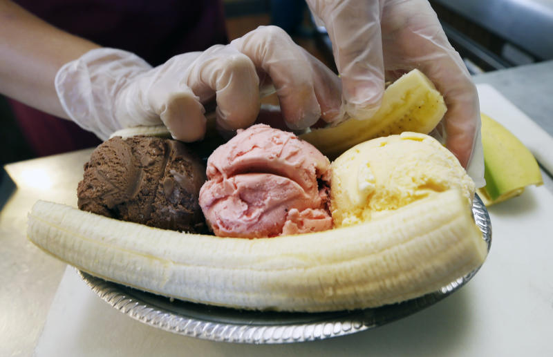 Kylie Polinsky places the other half of a split banana behind the three scoops of ice cream as she prepares a banana split sundae Wednesday Aug. 21, 2013, at the Valley Dairy in Latrobe, Pa. A weekend of festivities are planned to surround the dedication of a Pennsylvania Historical and Museum Commission marker to be dedicated Friday, Aug. 23 that acknowledges apprentice pharmacist David E. Strickler for inventing the banana split there in 1904. (AP Photo/Keith Srakocic)