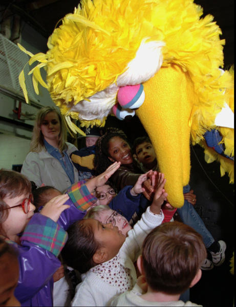 FILE - In this March 20, 1998, file photo, students from the Overbrook School for the Blind reach up and touch the beak of Sesame Street's Big Bird character before his performance in Philadelphia. Officials with SeaWorld Entertainment and Sesame Workshop announced Monday, Oct. 21, 2019, that they are opening the country's second Sesame Place park in San Diego in 2021. The first Sesame Place opened almost 40 years ago outside Philadelphia. (AP Photo/Chris Gardner, File)