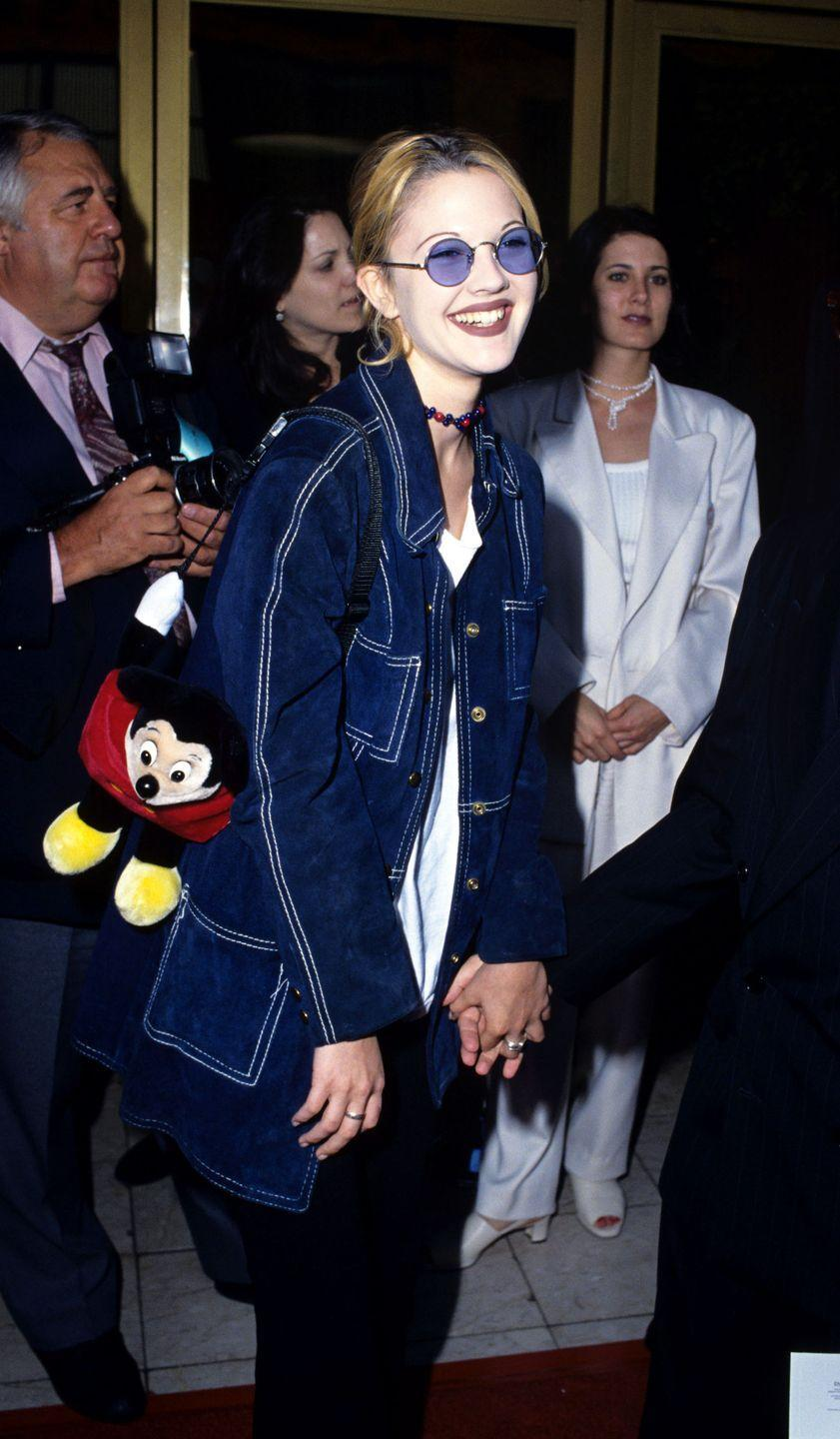 <p>Ever seen a plush Mickey backpack on a red carpet? Yeah, neither have I until I was blessed with this photo of Drew. She was all smiles with her Disney pal by her side and wore a jacket with white contrast stitching, round tinted sunglasses, and a choker. </p>