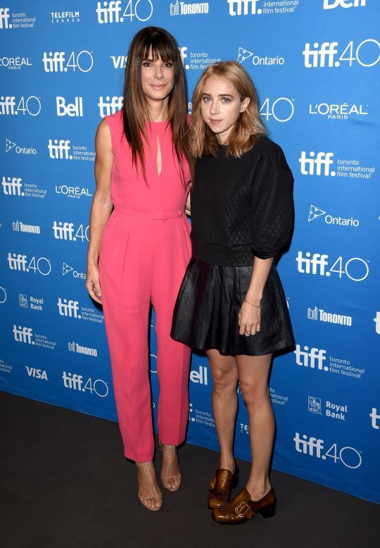 "<p>Co-stars Sandra Bullock and Zoe Kazan stuck close at the ""Our Brand Is Crisis"" press conference at the 2015 Toronto International Film Festival. While Kazan was super casual in a black skirt and leather brogues, Bullock, on the other hand, popped in a bright pink jumpsuit.</p>"