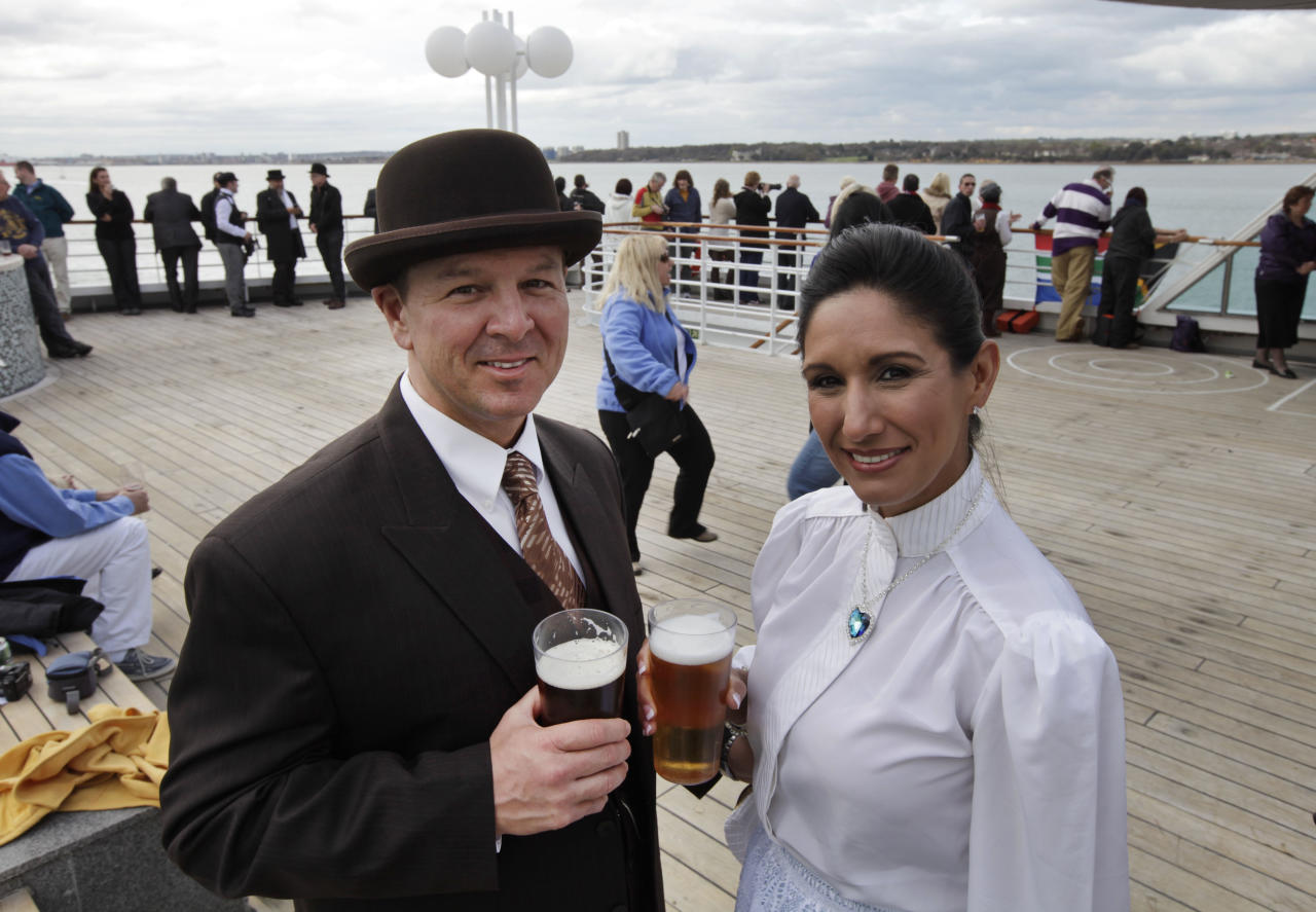 Passengers wearing costumes pose for pictures as the MS Balmoral Titanic memorial cruise ship sail from Southampton, England, on Easter Sunday, April 8, 2012. Nearly 100 years after the Titanic went down, a cruise with the same number of passengers aboard is setting sail to retrace the ship's voyage, including a visit to the location where it sank. The Titanic Memorial Cruise departed Sunday from Southampton, where the Titanic left on its maiden voyage and the 12-night cruise will commemorate the 100th anniversary of the sinking of the White Star liner. With 1,309 passengers aboard, the MS Balmoral will follow the same route as the Titanic and organizers are trying to recreate the onboard experience minus the disaster from the food to a band playing music from that era. (AP Photo/Lefteris Pitarakis)