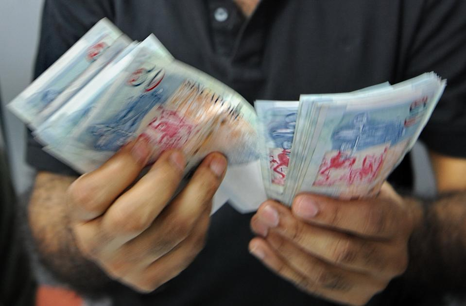 A money changer counting Singapore currency. (Photo: AFP)