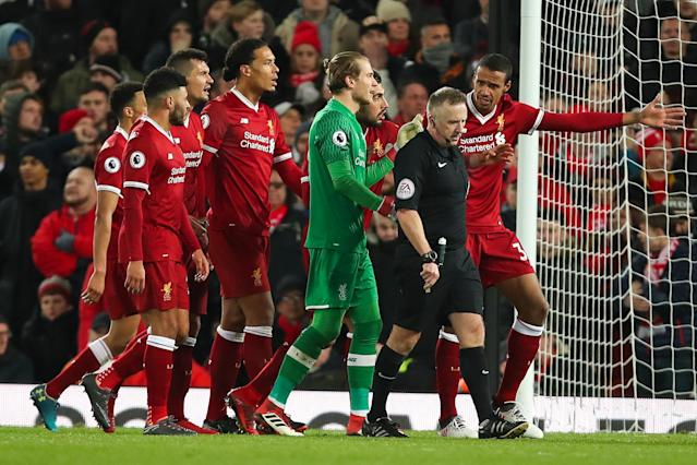 Liverpool players hound referee John Moss after one of two controversial penalty decisions against them. (Getty)