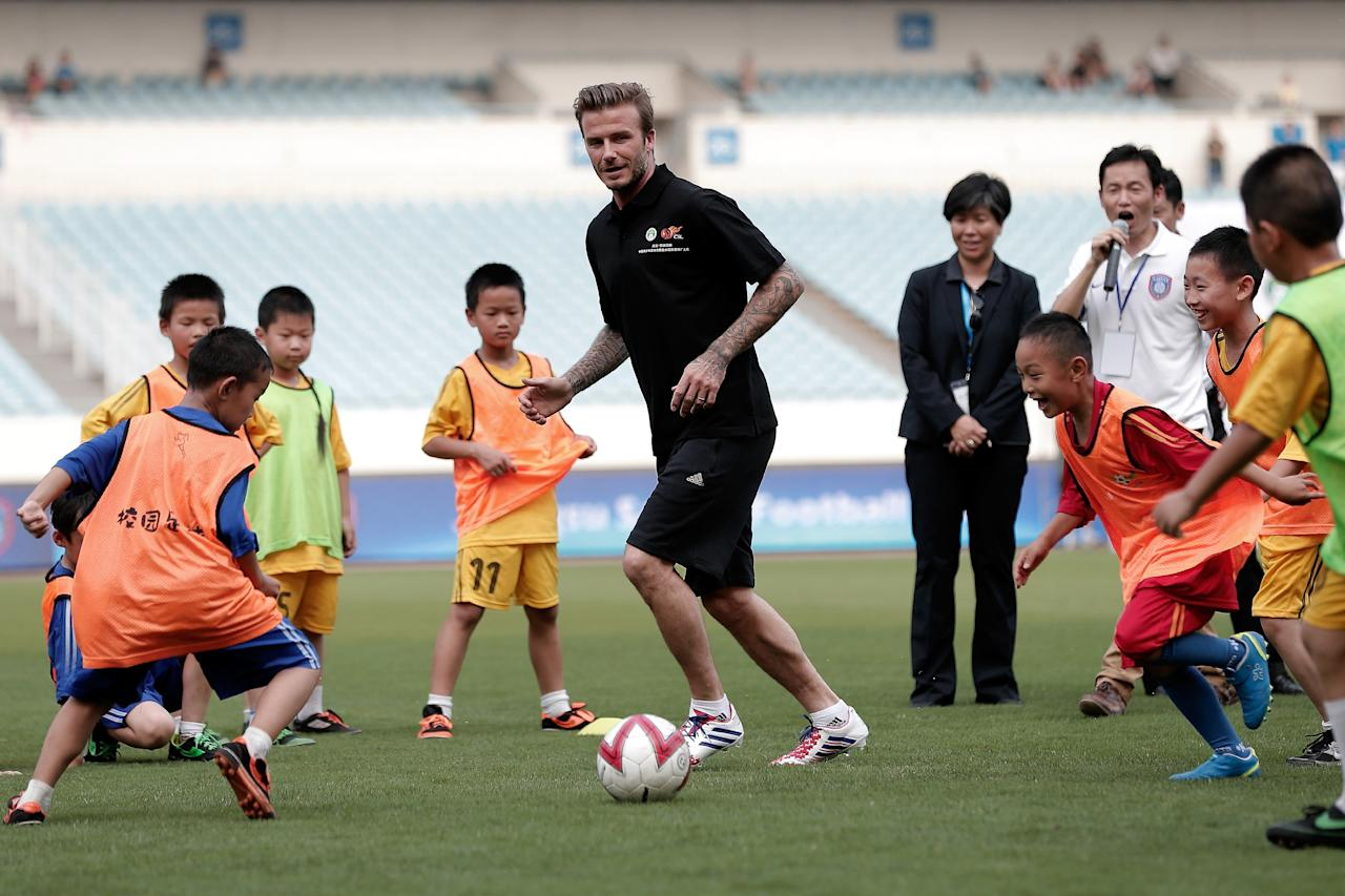 BEIJING, CHINA - JUNE 18:  David Beckham plays football with young children at Nanjing Olympic Sports Center on June 18, 2013 in Nanjing, Jiangsu Province of China.   (Photo by Lintao Zhang/Getty Images)