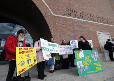 Protesters hold up signs outside federal court in Boston, Thursday, Dec. 18, 2014, where the final hearing for Boston Marathon bombing suspect Dzhokhar Tsarnaev was held before his trial begins in January. Tsarnaev is charged with carrying out the April 2013 attack that killed three people and injured more than 260. He could face the death penalty if convicted. (Elise Amendola/(AP Photo)