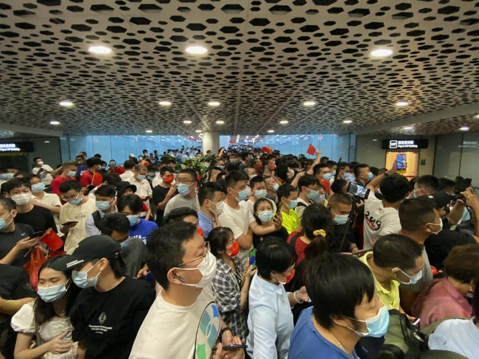 A crowd of people wearing masks gather in an airport arrival hall.