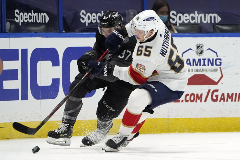 Florida Panthers defenseman Markus Nutivaara (65) takes the puck from Tampa Bay Lightning center Yanni Gourde (37) during the second period of an NHL hockey game Saturday, April 17, 2021, in Tampa, Fla. (AP Photo/Chris O'Meara)